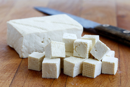 Photo for Single block of white tofu with cut tofu cubes and rustic knife on wooden chopping board. - Royalty Free Image