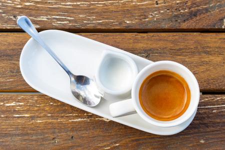 Foto de Espresso in white ceramic cup next to milk and spoon on rustic wooden table from above. - Imagen libre de derechos