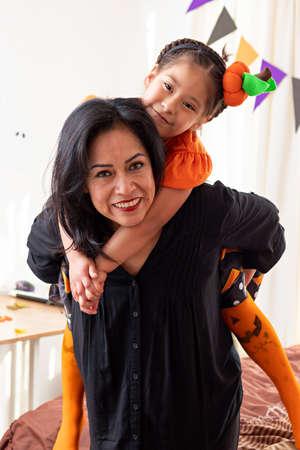Foto de A smiling woman carrying a girl looking at the camera in disguise of halloween - Imagen libre de derechos