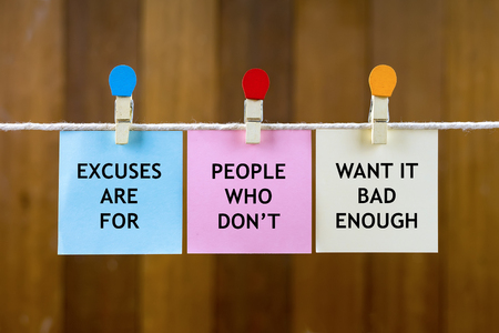 Foto de Word quotes of EXCUSES ARE FOR PEOPLE WHO DON'T WANT IT BAD ENOUGH on colorful sticky papers hanging by a rope against blurred wooden background. - Imagen libre de derechos