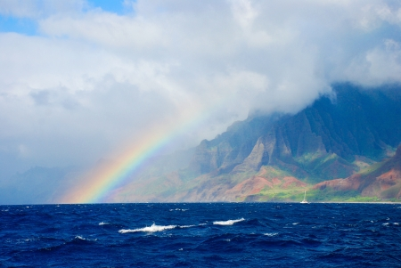 Foto de rainbow and storm over the Napali Coast with deep blue ocean and warm afternoon light over the mountains - Imagen libre de derechos