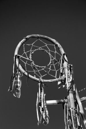 Black and white, close-up image of native American dream catcher made from willow, feathers and beads against a clear dark sky