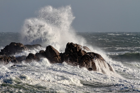 Foto de Big waves crashing against rocks in a windy afternoon - Imagen libre de derechos