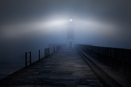 Photo for River mouth lighthouse and granite pier in a foggy night - Royalty Free Image