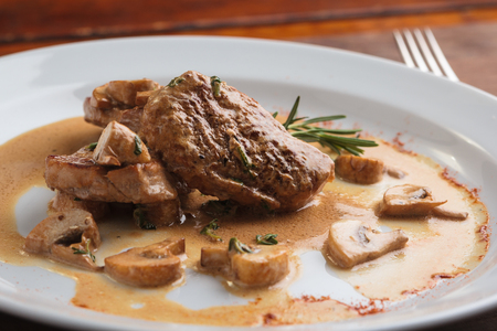 Photo pour Concept: restaurant menus, healthy eating, homemade, gourmands, gluttony. White plate of pork medallions with mushroom sauce on weathered wooden table. - image libre de droit