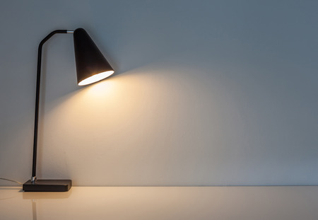 Photo for The modern desk lamp illuminate on the wall background. (left the space for text) - Royalty Free Image
