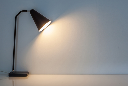 Foto de The modern desk lamp illuminate on the wall background. (left the right space for text) - Imagen libre de derechos
