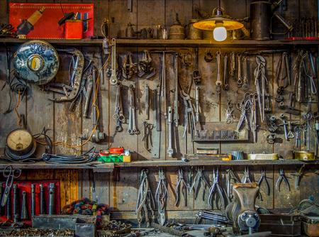 Foto de Vintage Tools Hanging On A Wall In A Tool Shed Or Workshop - Imagen libre de derechos