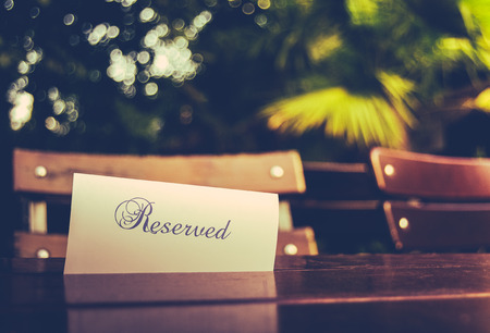 Photo pour Vintage Styled Image Of A Reserved Sign On A Table At An Outdoor Restaurant - image libre de droit