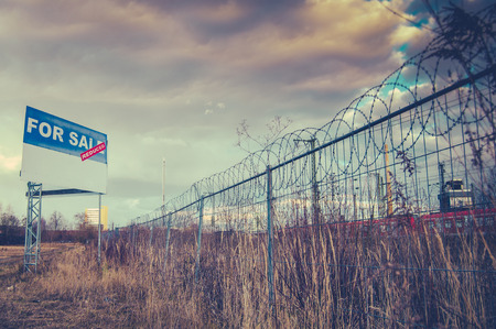 Photo pour A For Sale Billboard Sign In An Urban Industrial Wasteland Or Vacant Lot - image libre de droit