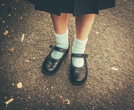 Photo pour Retro Style Image Of School Girl's Feet In Uniform - image libre de droit