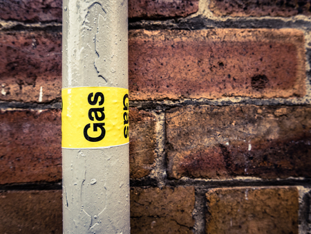 Photo for Detail Of A Residential Gas Pipe Against A Red Brick Wall - Royalty Free Image