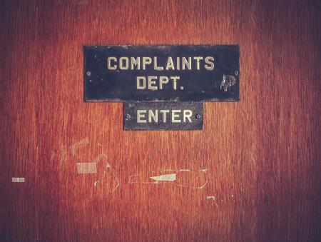 Photo pour Retro Filtered Image Of A Grungy Complaints Department Sign On A Door - image libre de droit