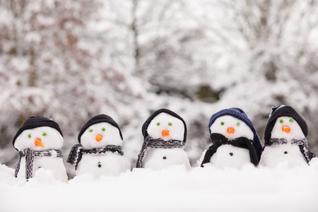 Foto de Five cute snowmen dressed for winter, all facing forward and sat on snow. Snowmen wearing hats and scarfs with carrot noses. Winter scene in the background with trees covered. - Imagen libre de derechos