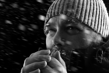 Foto de Freezing cold man standing in a snow storm biazzard trying to keep warm. Wearing a beanie hat and winter coat with frost and ice on his beard and eyebrows. Black and white. - Imagen libre de derechos