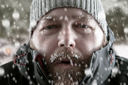 Foto de Freezing cold man standing in a snow storm blizzard trying to keep warm. Wearing a beanie hat and winter coat with frost and ice on his beard and eyebrows staring at the camera. - Imagen libre de derechos