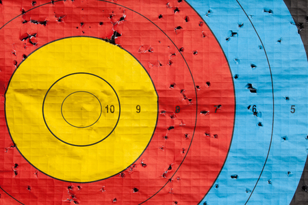 Photo pour Missed the target concept with large target peppered with holes except the gold bullseye - image libre de droit