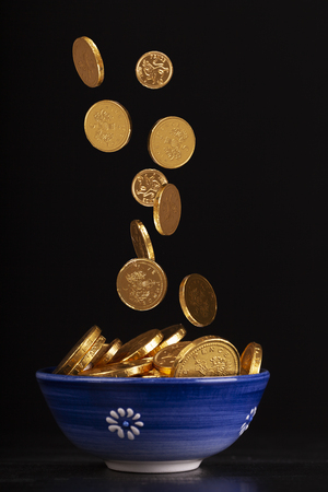 Foto de Pot of gold concept with chocolate gold coins falling in to a pot on a black background - Imagen libre de derechos