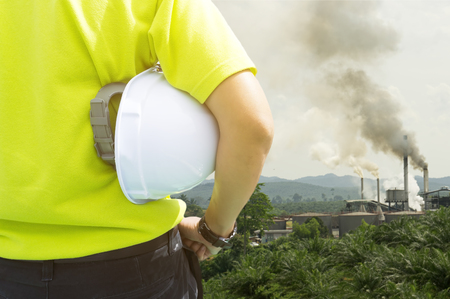 Foto de Safety and Health in workplace concept - Engineering man or Safety Inspector standing and looking to air pollution from palm oil mill - Imagen libre de derechos