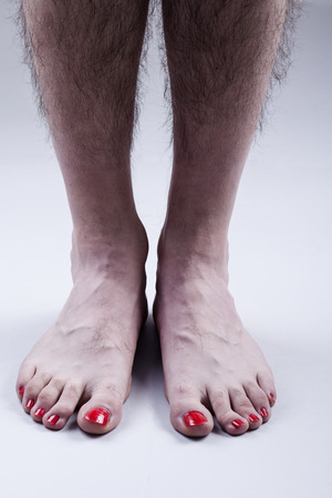Foto de Man's Feet with Red Nail Polish and Hairy Legs on Bright Gray Background - Imagen libre de derechos