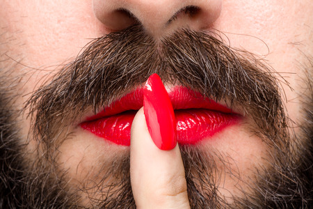Photo pour Bearded Man with Red Lipstick on His Lips and Nail Polish Making Silence Gesture - image libre de droit