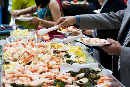Photo of cooked shrimp and crab legs served at a wedding during cocktail hour. This image has a very shallow depth of field.