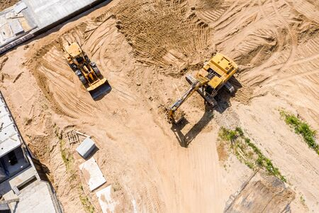 Foto de aerial top view of yellow industrial heavy machines moving ground at construction site - Imagen libre de derechos