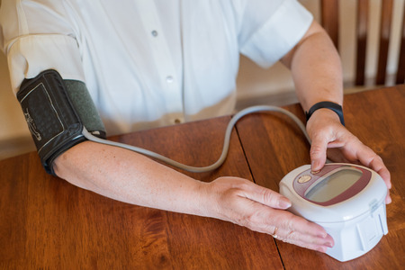 Foto de An elderly woman measures blood pressure with an electrical device. A pensioner uses a tonometer. Hands of an old woman. - Imagen libre de derechos