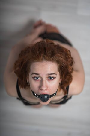 Photo for Slavery in society. The girl is on her knees with a gag in her mouth. Sexual bdsm toy. Woman slavery. Slave attire for playing bdsm games. Frightened slave. Black leather bondage with gag. Scared hostage - Royalty Free Image