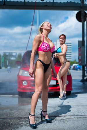 Foto per Luxury girls in seductive bikinis wash a car in a street car wash and water each other. Blonde and red-haired with beautiful figures wash a red car at a manual car wash. Self-care, dry cleaning salon. - Immagine Royalty Free