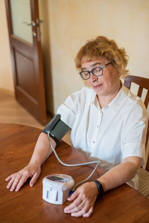 Foto per An elderly woman with glasses measures blood pressure using an electrical device in a bright room. Retired woman in a white blouse uses a tonometer at home sitting at the table - Immagine Royalty Free