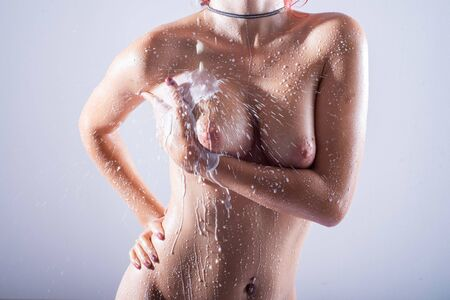 Foto de Close-up of a naked female breast with drops of milk. White water flows down the mammary glands of a beautiful girl. Gorgeous boobs in droplets. Wet nude woman with a beautiful figure. - Imagen libre de derechos