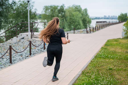 Photo pour An obese young woman jogging outdoors. Fat beautiful smiling girl in a black tracksuit is engaged in fitness for weight loss on the waterfront. A woman runs on a summer day. - image libre de droit