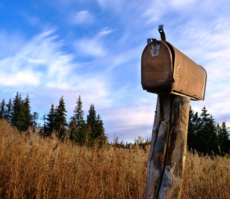 Foto de A rusty old rural mailbox on a wooden post in dry grass with spruce in the background and a bright blue sky with clouds - Imagen libre de derechos