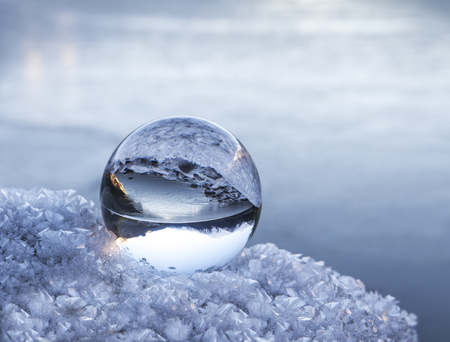 Photo pour Alaskan mountains and lake reflected in a glass ball on a frosty rock in winter. - image libre de droit