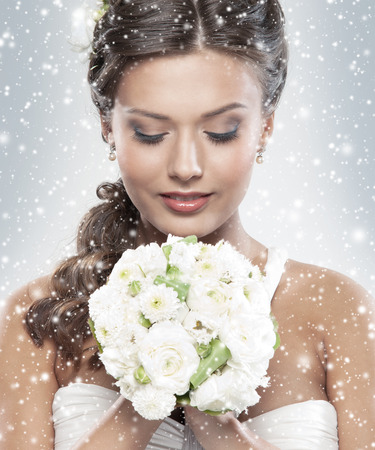 Photo for Young attractive bride with the bouquet of white roses over snowy Christmas background - Royalty Free Image