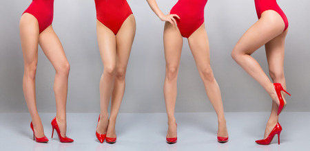 Beautiful legs of young and sporty woman in red swimsuit over grey background