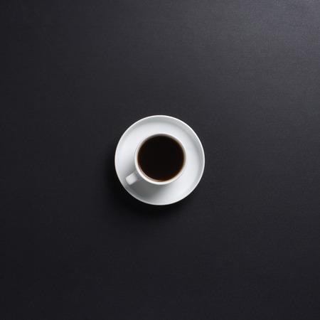 Photo pour Cup of coffee over the black background - image libre de droit