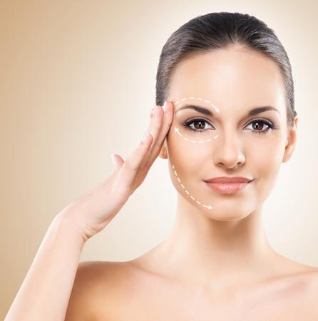Photo pour Spa portrait of a young and healthy woman with arrows on her face. Plastic surgery concept. - image libre de droit