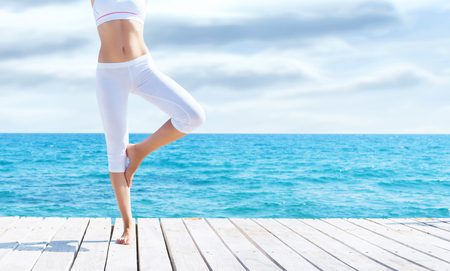 Photo for Attractive girl in white sporty clothes doing yoga on a wooden pier. Yoga, sport, leisure, recreation and freedom concept. - Royalty Free Image