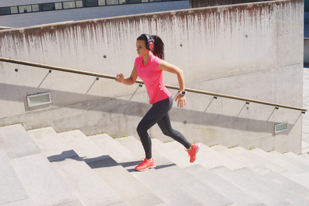 Photo pour Young, fit and sporty woman running up the stairs. Fitness, sport, urban jogging and healthy lifestyle concept. - image libre de droit