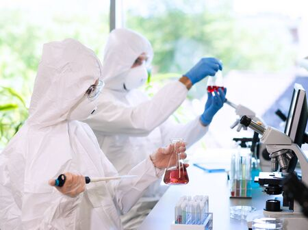 Foto de Scientists in protection suits and masks working in research lab using laboratory equipment: microscopes, test tubes. - Imagen libre de derechos
