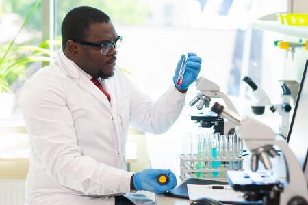 Foto de African-american medical doctor working in research lab. Science assistant making pharmaceutical experiments. Chemistry, medicine, biochemistry, biotechnology and healthcare concept. - Imagen libre de derechos