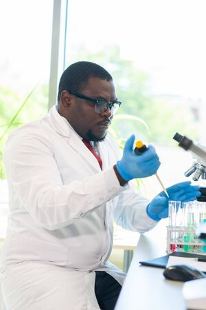 Foto de African-american scientist working in lab. Doctor making microbiology research. Laboratory tools: microscope, test tubes, equipment. Biotechnology, chemistry, bacteriology, virology, dna and health care concept. - Imagen libre de derechos