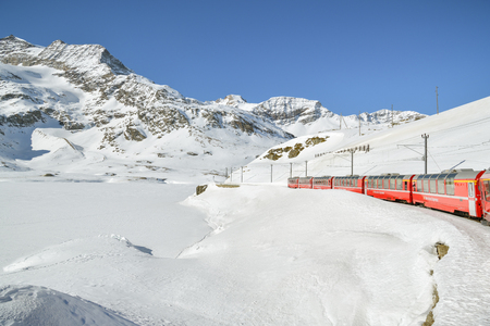 Foto de Bernina Pass, Switzerland - February 16, 2019: Typical red Bernina Express train riding through the Bernina pass, highest point of the route in Swiss Alps during February 2018 - Imagen libre de derechos