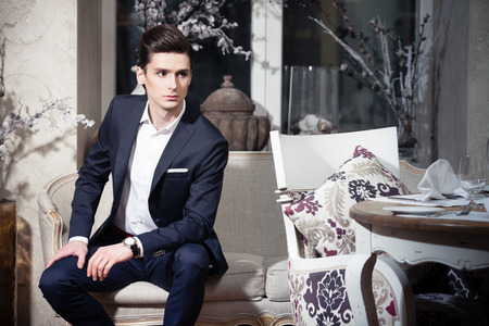 Photo for Handsome young man in a classic suit sitting on a sofa in restaurant - Royalty Free Image