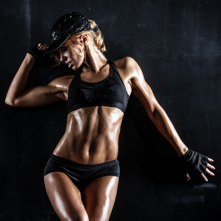Photo for Sexy fit woman in a cap posing on dark background - Royalty Free Image