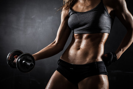 Foto de Brutal athletic woman pumping up muscles with dumbbells - Imagen libre de derechos