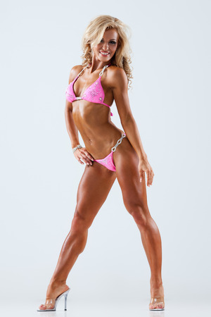 Foto de Smiling athletic woman in pink bikini showing muscles on gray  - Imagen libre de derechos