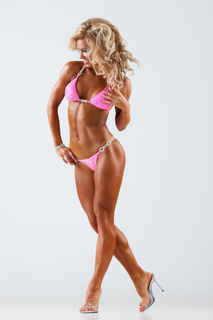 Photo for Smiling athletic woman in pink bikini showing muscles on gray background - Royalty Free Image